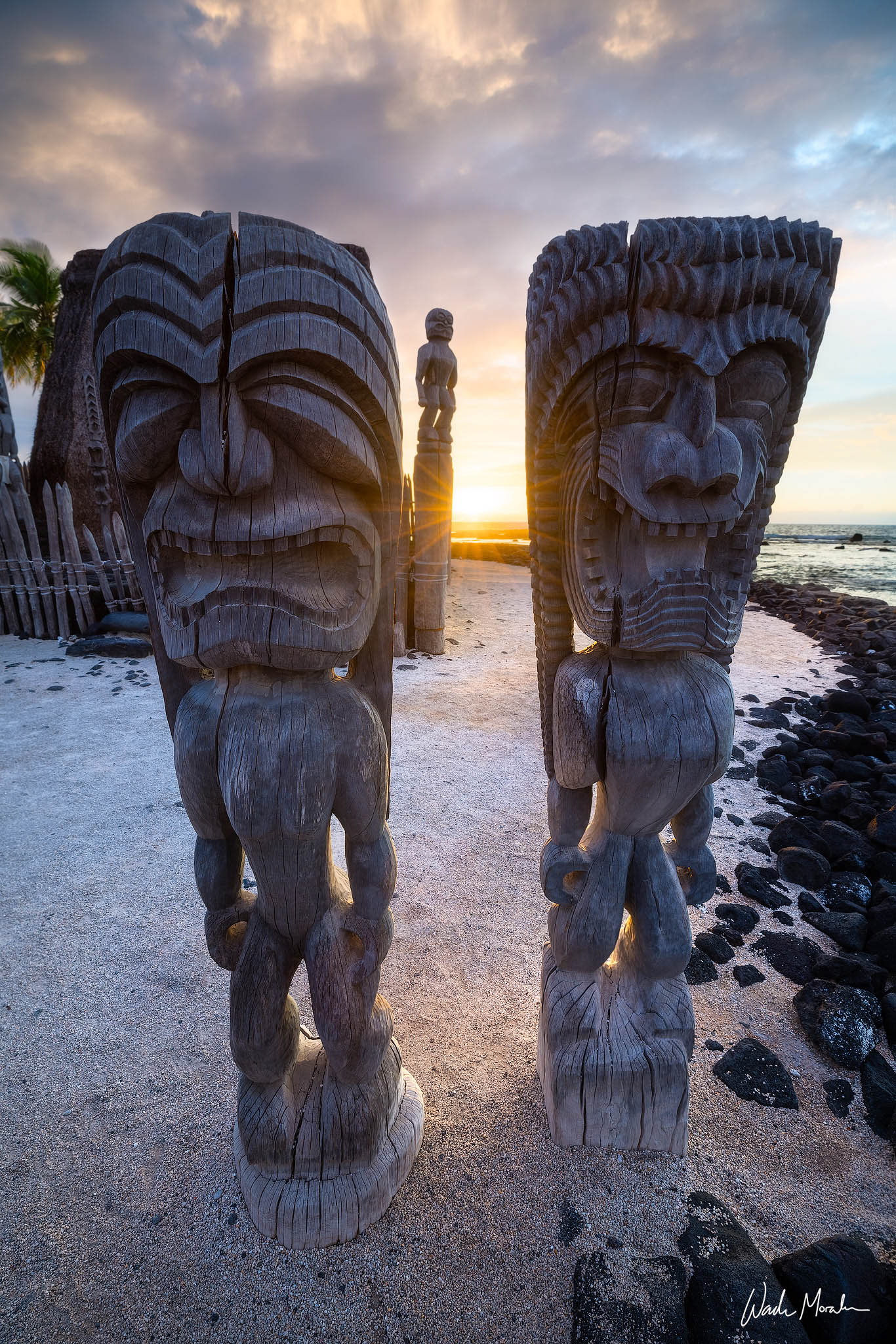 In this photo, I caught the sun setting in between two kiʻi statues in the City of Refuge National Historic Park. This was a...