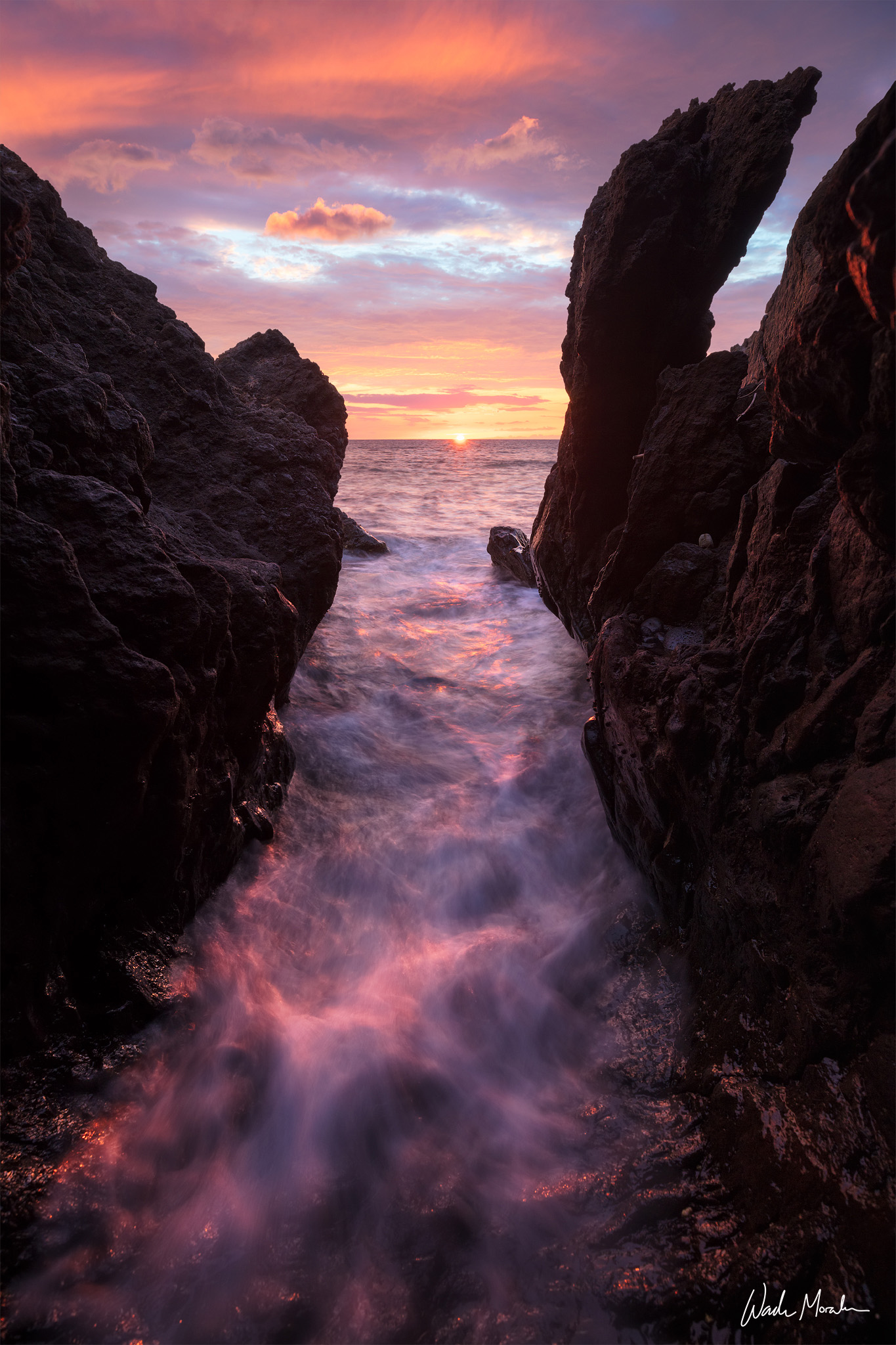 A crevice of eroded lava rock continuously channels water onto the beach and back out into the sea. During this sunset over the...