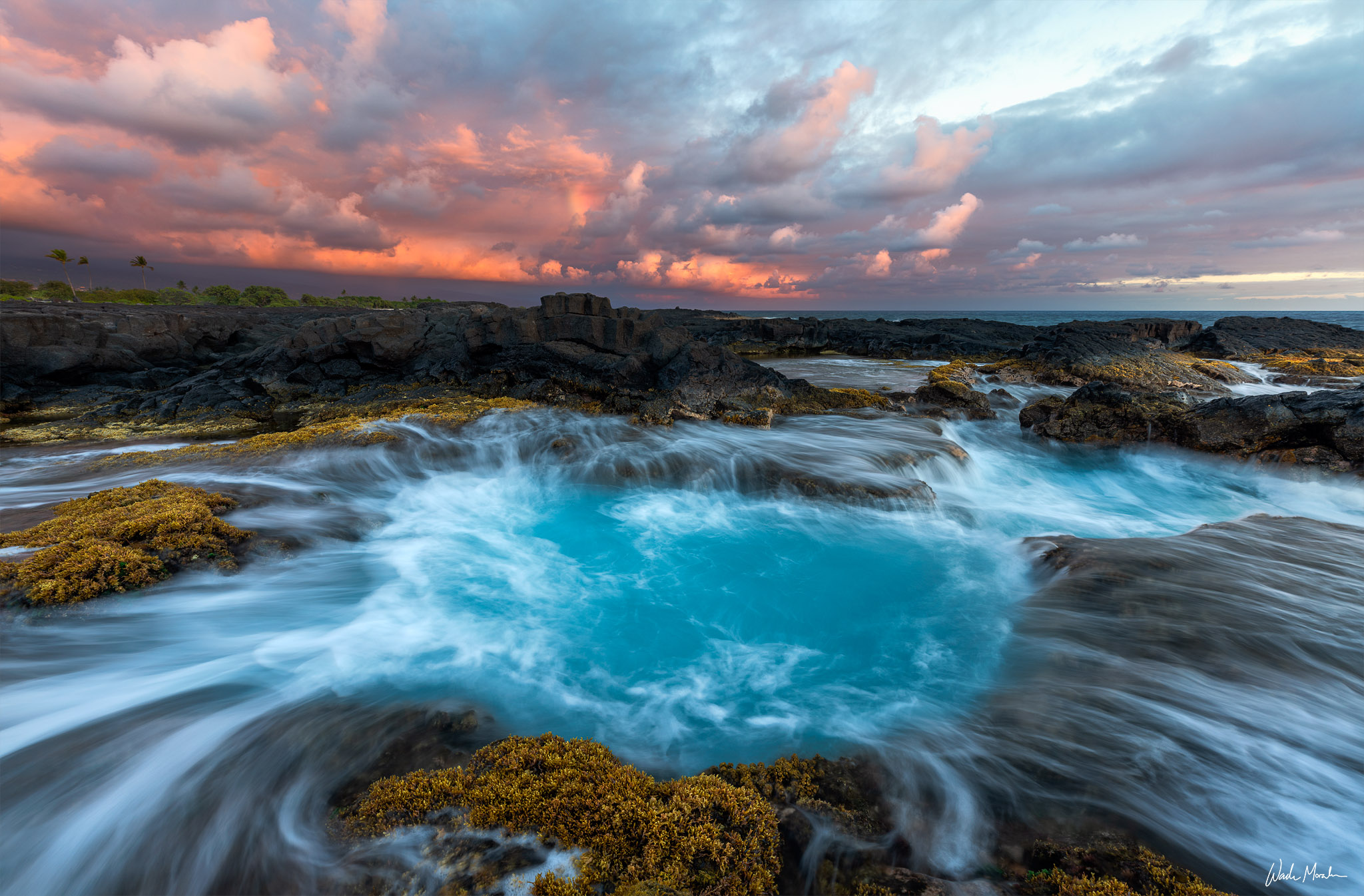 A collapsed lava tube fills up with water and drains back out to sea as the waves reach the shoreline of Kona, on the Big Island...