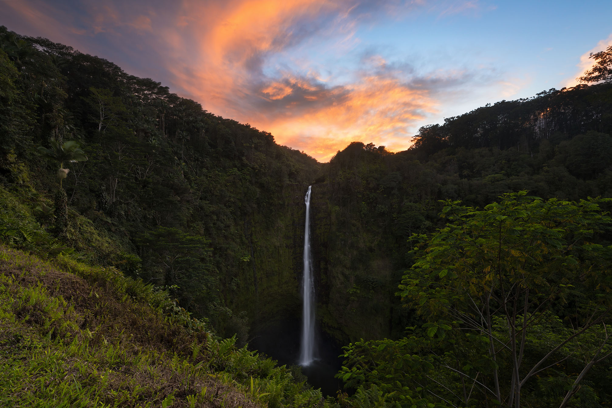 In this image a fiery sunset ignites over Akaka Falls waterfall on the Big Island of Hawaii. This photo is named Keahi which...