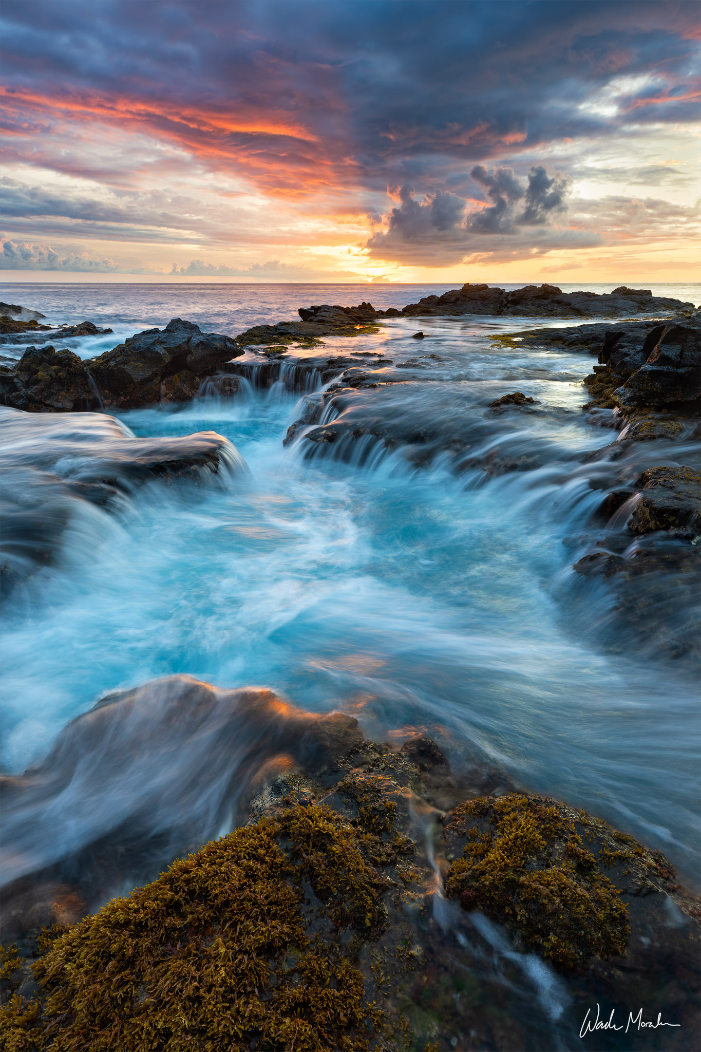 A lava tube fills and drains with tranquil blue water while being gently illuminated by the fleeting light of a Kona sunset....