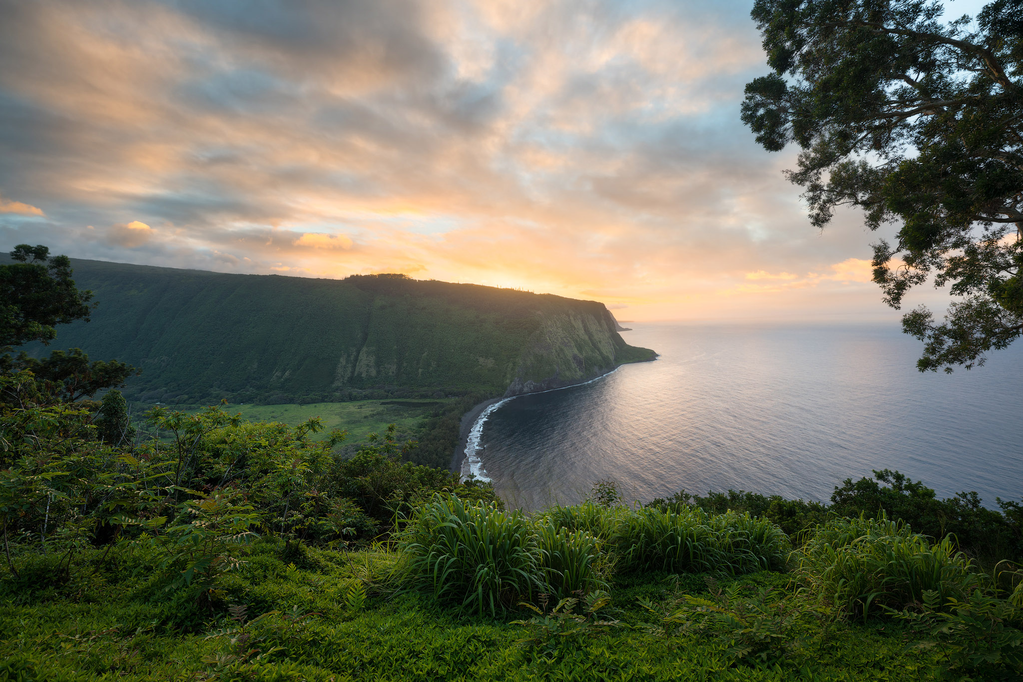 In this photo of Waipiʻo Valley a colorful sunset fills the sky over the Hamakua coastline.Waipiʻo Valley is a sacred place...